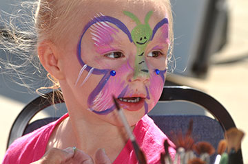 A girl is excited about getting her face painted at the Sunday Grand Blanc Farmers Market.
