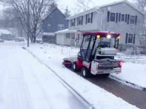 SnowBuddy's tractor can clear the sidewalk in front of a residential lot in approximately 10 seconds.  Photo courtesy Paul Tinkerhess.